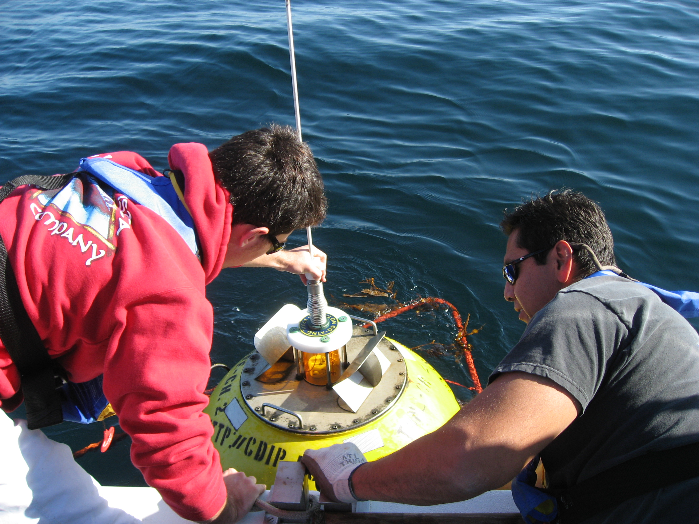 Victor holds old buoy while Andy unscrews antenna